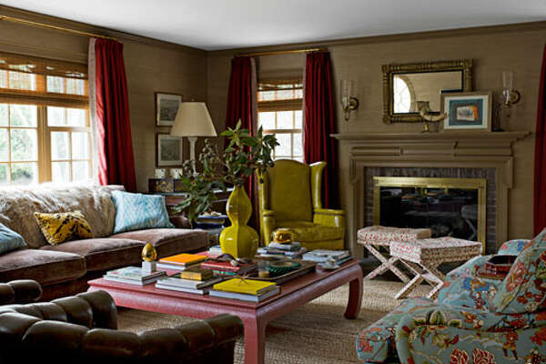 """Design Around the Fireplace    Designer Meg Braff oriented the seating in this Colonial Revival house in Lattingtown, New York, around the fireplace. """"When there's a fireplace in a room, you want to be around it,"""" Braff says. """"You can imagine a fire even if there isn't one."""" A large-scale coffee table from Meg Braff Antiques & Decorations anchors the sofa and the chairs. A vintage chartreuse leather wing chair adds snap. Walls are covered in a taupe grass cloth from Hinson."""