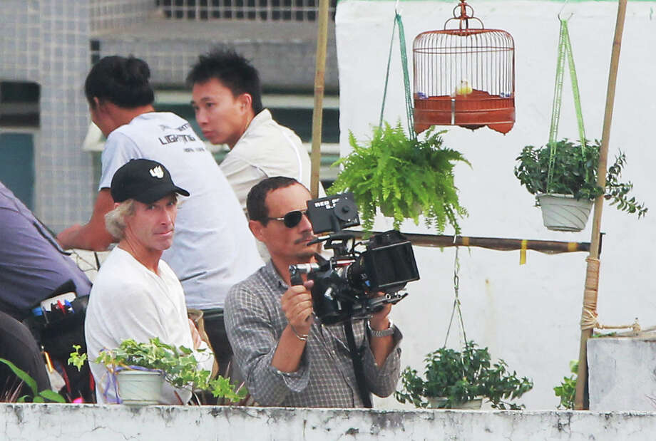 "American film director Michael Bay, left, assists the cameraman as they are filming their latest film ""Transformers Four"" in Hong Kong Thursday, Oct. 17, 2013. Two men have been arrested after the American film director, Michael Bay, was allegedly assaulted in Quarry Bay while working on his latest film, ""Transformers Four"" as the two men demanding money from the film crew. (AP Photo) ORG XMIT: XKC101 / AP"