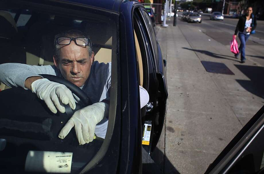 Aaron Lasnover works up a sweat while the late-model BMW he's detailing in San Francisco gradually loses its grime. Photo: Mike Kepka, The Chronicle