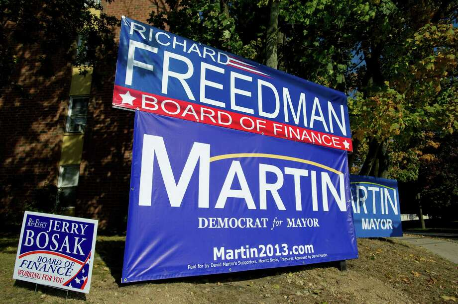 Large campaign signs for Board of Finance candidate Richard Freedman and mayoral candidate David Martin dwarf a nearby sign for Board of Finance candidate Jerry Bosak at the intersection of Courtland Ave. and Taylor Reed Place in Stamford, Conn., on Thursday, October 17, 2013.. Photo: Lindsay Perry / Stamford Advocate
