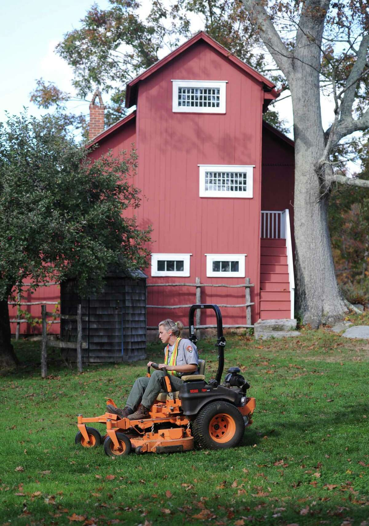 Historic Gardener Jill Anderson mows the grass outside Weir Studio at Weir Farm National Historic Site in Wilton, Conn. on Thursday, Oct. 17, 2013. The government-operated park re-opened Thursday with the end of the government shutdown. Employees and volunteers restored the property after more than two weeks off, allowing visitors to come back and enjoy the park.