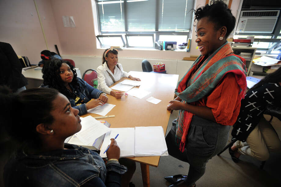 From left; Central High School seniors Stephanie Brown, 17, Lashaya Gibson, 18, and Shanna-Kaye McLarty-Jenkins, 16, talk about planning for college with Development Coordinator Askar Morisseau in the Student Space room at Central High School in Bridgeport, Conn. on Thursday, October 17, 2013. Photo: Brian A. Pounds / Connecticut Post