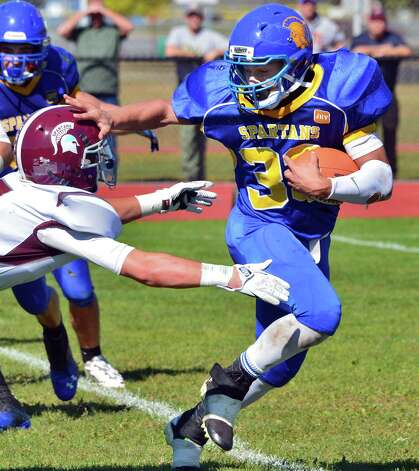 Queensbury's  #33 Brett Rodriguez, at right, dodges a tackle during their game against Burnt Hills Saturday Sept. 28, 2013, in Queensbury, NY. (John Carl D'Annibale / Times Union) Photo: John Carl D'Annibale / 00024014A