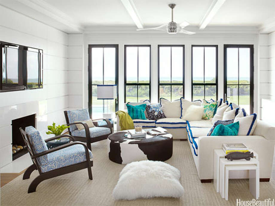 "Electric Color In this Sullivan's Island, South Carolina, vacation home, the family room's neutral sofa gets instant pizzazz with an electric blue brush fringe from Samuel & Sons. ""Brush fringe used as welting turns out to be fresh and fun—and electric blue is my new favorite color,"" designer Sally Markham says. The room is completed with vintage Russel Wright chairs upholstered in Meloire Reverse by China Seas and a Calypso Home floor pillow. Photo: THOMAS LOOF, HouseBeautiful.com"