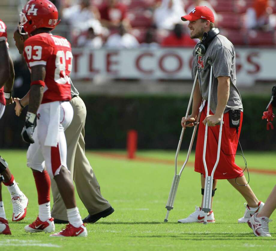 Injured Houston quarterback Case Keenum jokes with teammates during a time out in the second quarter of his game against Tulane University Saturday, Sept. 25, 2010, in Robertson Stadium in Houston. Photo: Nick De La Torre, Houston Chronicle / Houston Chronicle