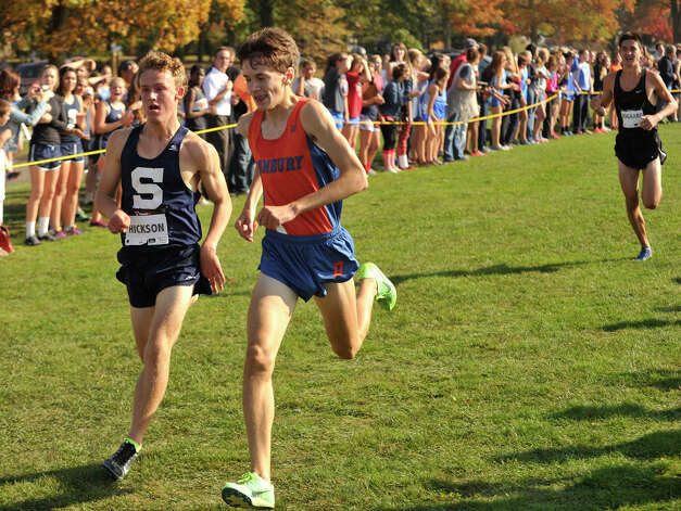 Staples' Oliver Hickson, left, edges out Danbury's Corey Mullins to claim sixth and seventh place respectively as Ridgefield's Kristian Sogaard, right, attains eighth place during the FCIAC boys varsity cross country championships at Waveny Park in New Canaan, Conn., on Thursday, Oct. 17, 2013. Photo: Jason Rearick / Stamford Advocate