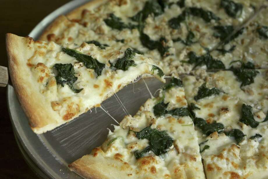The ricotta pizza at Figlio's Pizzeria includes grilled chicken, spinach, mozzarella — and ricotta, of course. Photo: Photos By Helen L. Montoya / San Antonio Express-News