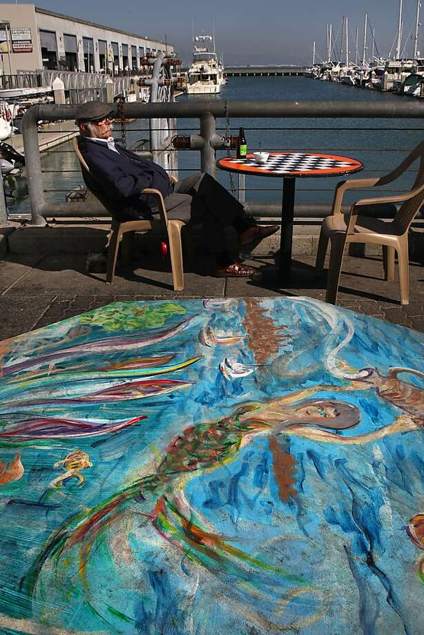 A hand painted table welcomes customers to Java House, while owner Philip Papadopoulos relaxes bayside on a sunny San Francisco afternoon. Photo: Liz Hafalia, The Chronicle