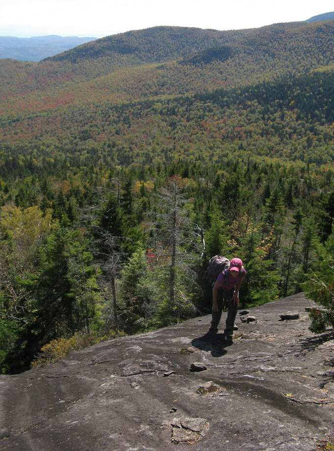 Photo by Herb Terns A hiker makes her way up the last pitch of Knob Lock in the Adirondacks.