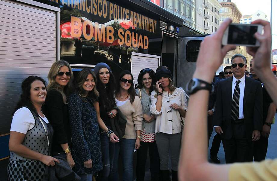 Erica Galland (left), Lee Anne Pope, Shayne Young, Andie Petersen, Jen Brotherson, Stephanie Santiago and Joelle Slade have a photo taken in front of the S.F. bomb squad vehicle when a bomb scare shut down Union Square. Photo: Leah Millis, The Chronicle