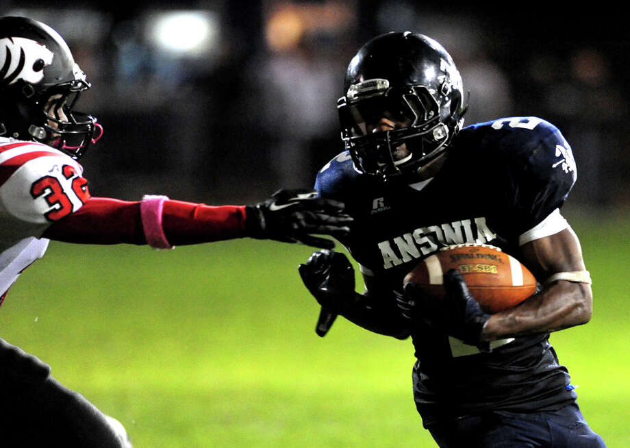 Masuk's Dorian Thompson reaches out to grab Ansonia's Arkeel Newsome, during football action in Ansonia, Conn. on Thursday October 17 2013. Photo: Christian Abraham / Connecticut Post