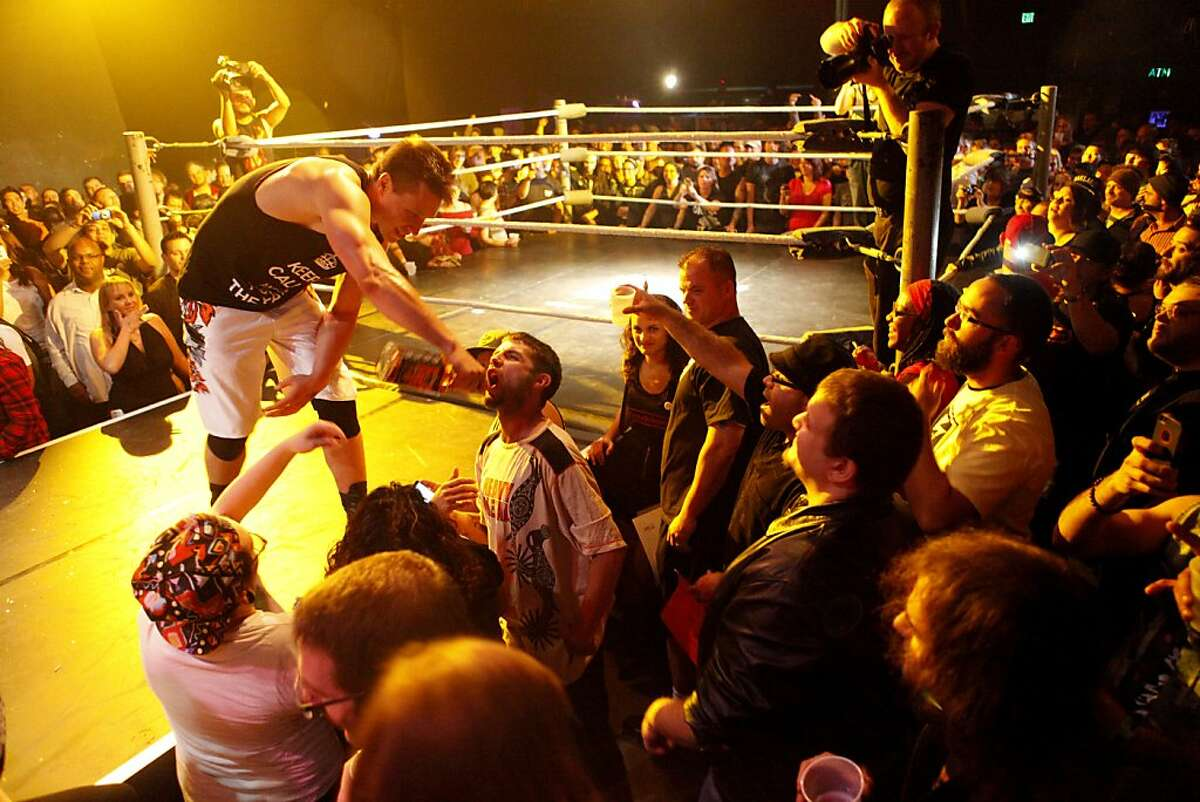 A.J. Kirsch pours shots of whiskey into fans mouths at Hoodslam, a wrestling entertainment event, held at the Oakland Metro Operahouse in Oakland, Calif. on August 2, 2013.