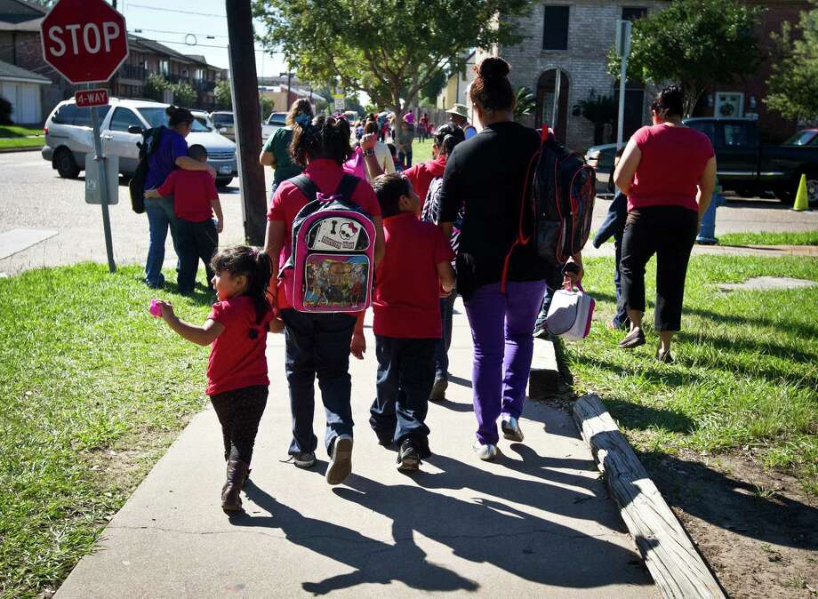 Parents and children walk home Thursday from Elrod Elementary, one of the schools losing magnet funding. Photo: Marie D. De Jeséºs, Staff / © 2013 Houston Chronicle