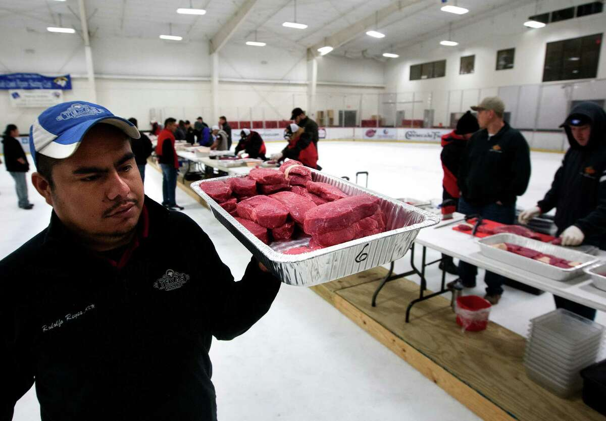Texas Roadhouse employee Rodolfo Reyes from the Pearland store carries steaks to be sorted during the A1 National Meat Cutting Challenge at the Sugar Land Ice & Sports Center.