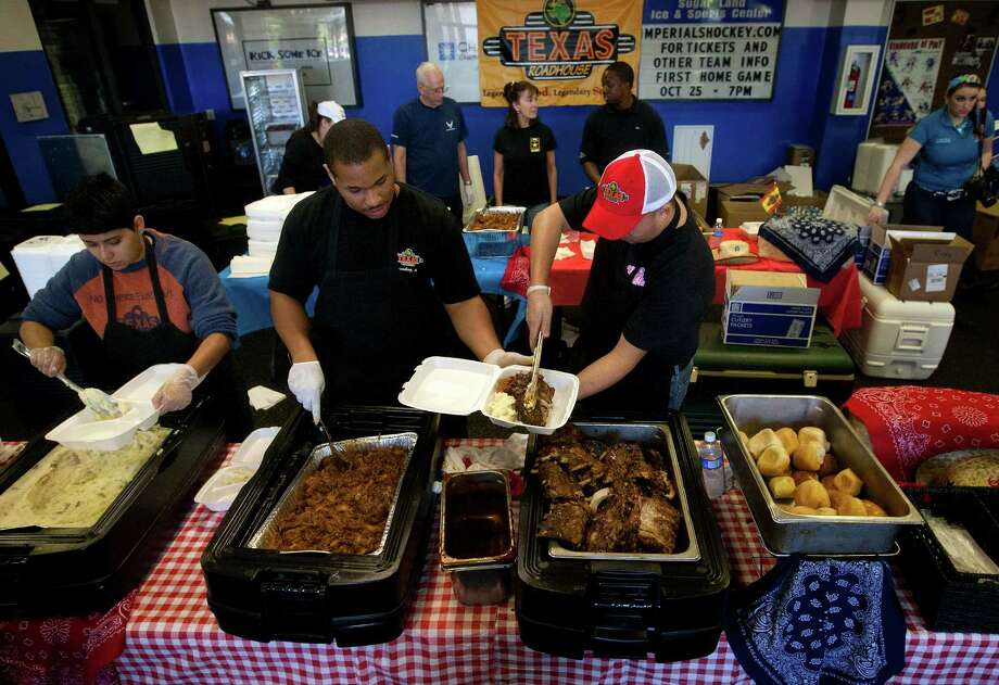 Texas Roadhouse employees Adriana Guzman, left, Kentrell Blunt, center, and Bobby Palacios, right, prepare meals during the A1 National Meat Cutting Challenge at the Sugar Land Ice & Sports Center. Photo: Cody Duty, Houston Chronicle / © 2013 Houston Chronicle