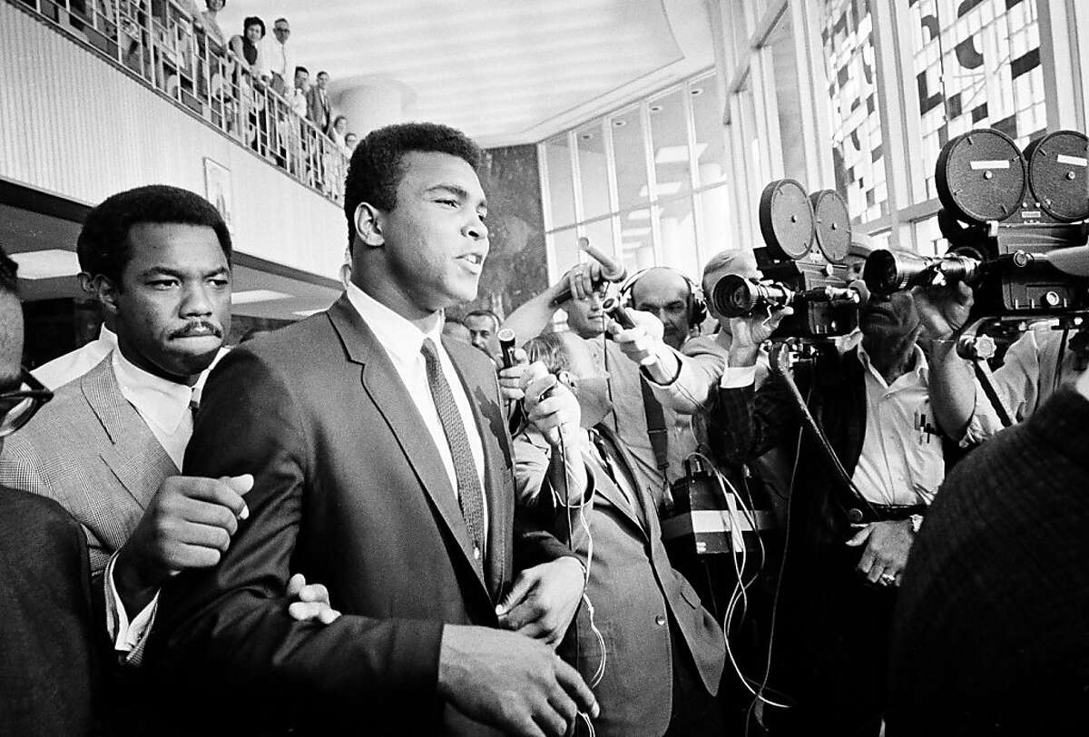 """FILE - In this June 19, 1967 file photo, heavyweight boxing champion Muhammad Ali has a """"no comment"""" as he is confronted by newsmen as he leaves the Federal Building in Houston during a recess in his trial for refusing induction to the army. Barely past the opening credits of a new documentary about Ali, we get a glimpse of how many Americans felt about him during a tumultuous time in the country's history. (AP Photo/Ed Kolenovsky, File)"""