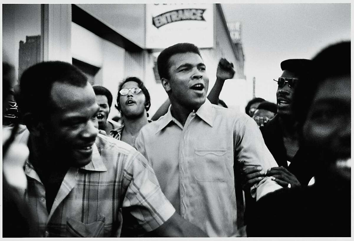 """Muhammad Ali walks through the streets of New York City with members of the Black Panther Party in September 1970. As seen in the documentary """"the Trials of Muhammad Ali."""" American heavyweight boxing champion Muhammad Ali walks through the streets with members of the Black Panther Party, New York, New York, September 1970. Ali was sentenced to five years in prison and his championship title revoked after he was convicted of draft evasion upon his refusal to serve with the American army in Vietnam upon grounds of conscientious objection. The decision was overtuned in 1971 but Ali became a figurehead of resistance and a hero of the people."""