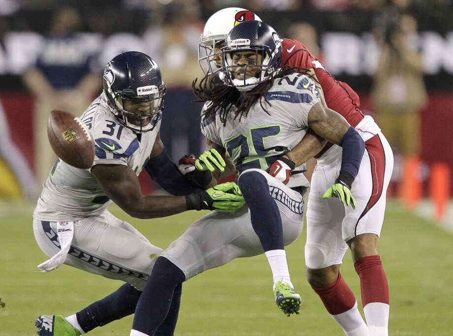 Seattle Seahawks cornerback Richard Sherman (25) breaks up a pass intended for Arizona Cardinals wide receiver Michael Floyd as Seahawks' Kam Chancellor (31) looks on during the first half of an NFL football game, Thursday, Oct. 17, 2013, in Glendale, Ariz. (AP Photo/Rick Scuteri) Photo: AP