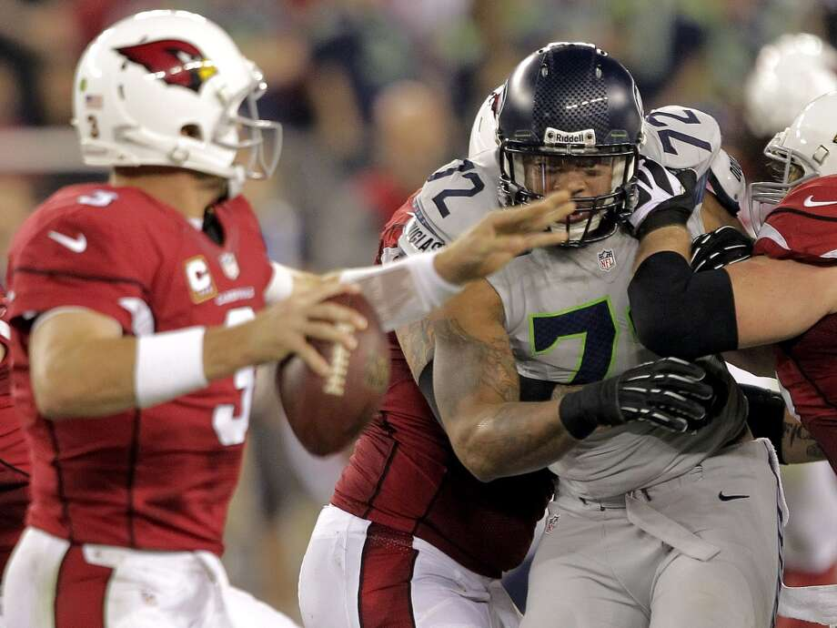 Arizona Cardinals quarterback Carson Palmer (3) is pressured by Seattle Seahawks defensive end Michael Bennett (72) during the first half of an NFL football game, Thursday, Oct. 17, 2013, in Glendale, Ariz. (AP Photo/Rick Scuteri) Photo: AP