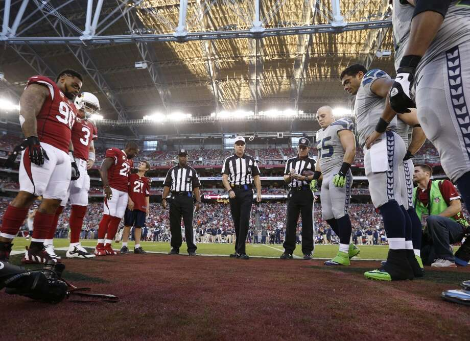 Referee Terry McAulay (77), center, performs the coin toss prior to a NFL football game between the Seattle Seahawks and the Arizona Cardinals the, Thursday, Oct. 17, 2013, in Glendale, Ariz. (AP Photo/Ross D. Franklin) Photo: AP
