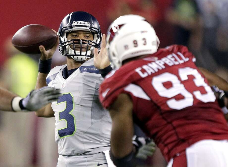 Seattle Seahawks quarterback Russell Wilson (3) throws under pressure from Arizona Cardinals' Calais Campbell (93) during the first half of an NFL football game, Thursday, Oct. 17, 2013, in Glendale, Ariz. (AP Photo/Rick Scuteri) Photo: AP