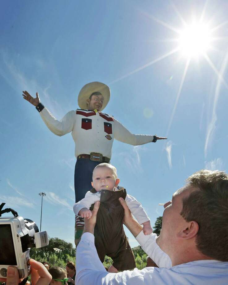 Big Tex bounced back and returned to the Texas State Fair after he caught fire in 2012. Now, he's getting a brand new outfit for the 2014 fair.Bill Quinn, right, holds up his 10-month-old son Henry Quinn for a his wife to make a photo in front of Big Tex at the State Fair of Texas in Dallas, Thursday, Oct. 17, 2013. Photo: LM Otero, Associated Press / AP