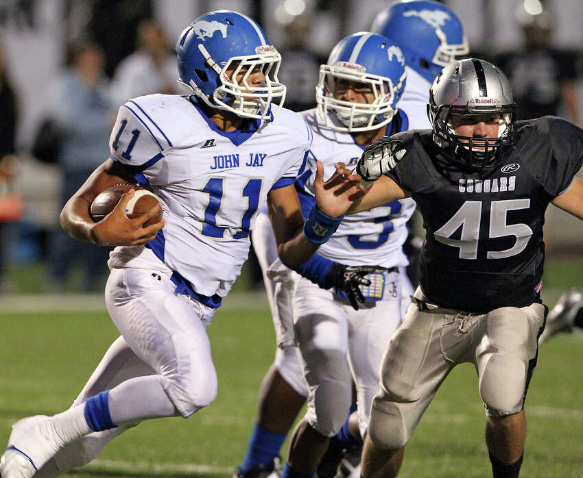 Mustang quarterback Moses Reynolds sprints around the right side with Zach Wood in pursuit as Jay plays Clark at Farris Stadium on October 17, 2013.