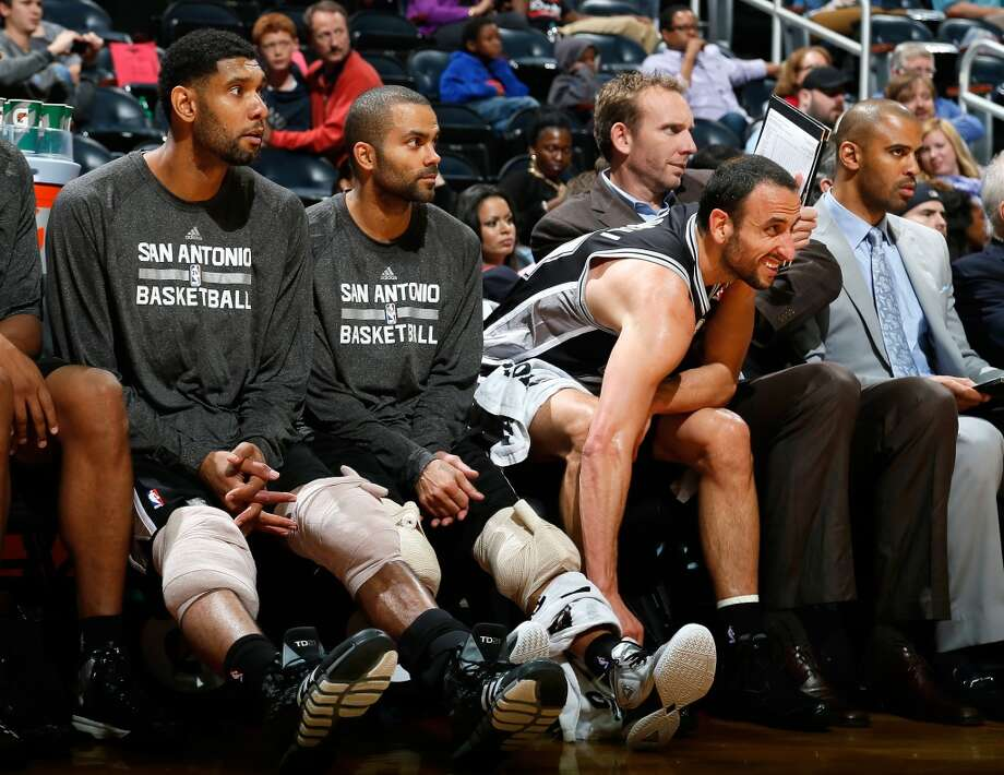 Tim Duncan #21, Tony Parker #9 and Manu Ginobili #20 of the San Antonio Spurs sit on the bench during the game against the Atlanta Hawks at Philips Arena on October 17, 2013 in Atlanta, Georgia. Photo: Kevin C. Cox, Getty Images