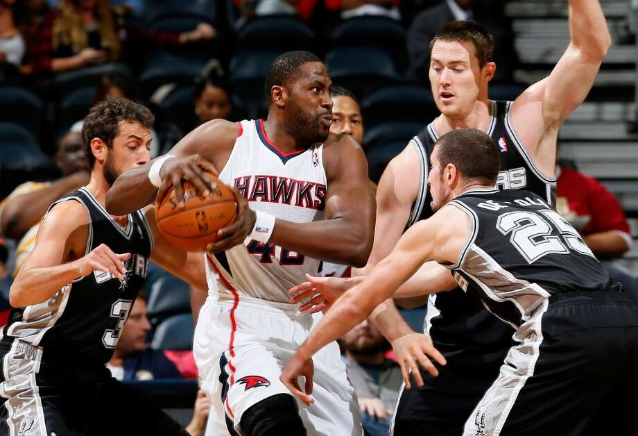 Elton Brand #42 of the Atlanta Hawks is defended by Marco Belinelli #3, Nando de Colo #25 and Aron Baynes #16 of the San Antonio Spurs at Philips Arena on October 17, 2013 in Atlanta, Georgia. Photo: Kevin C. Cox, Getty Images