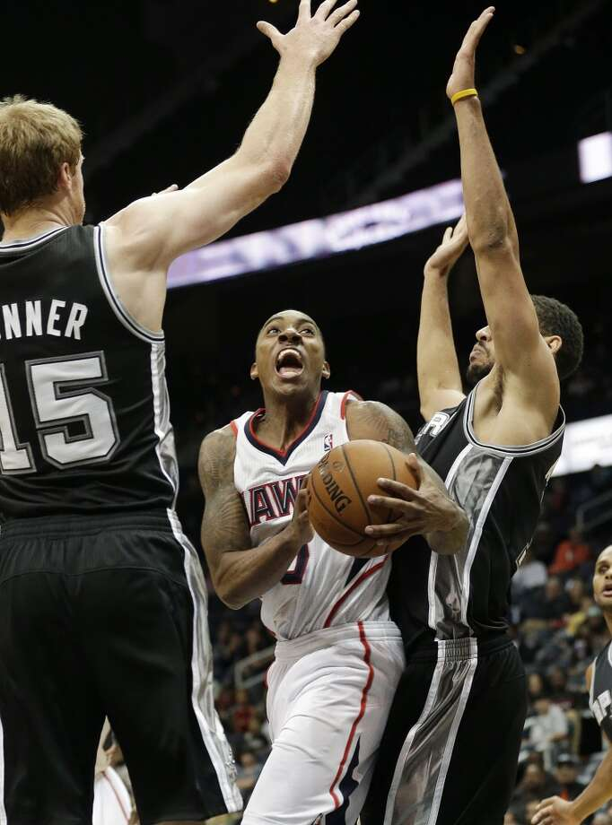 Atlanta Hawks point guard Jeff Teague (0) tries to get between San Antonio Spurs power forward Matt Bonner (15) and Jeff Ayres (11) in the second half of a preseason NBA basketball game, Thursday, Oct. 17, 2013 in Atlanta.  San Antonio won 106-104. Photo: John Bazemore, Associated Press