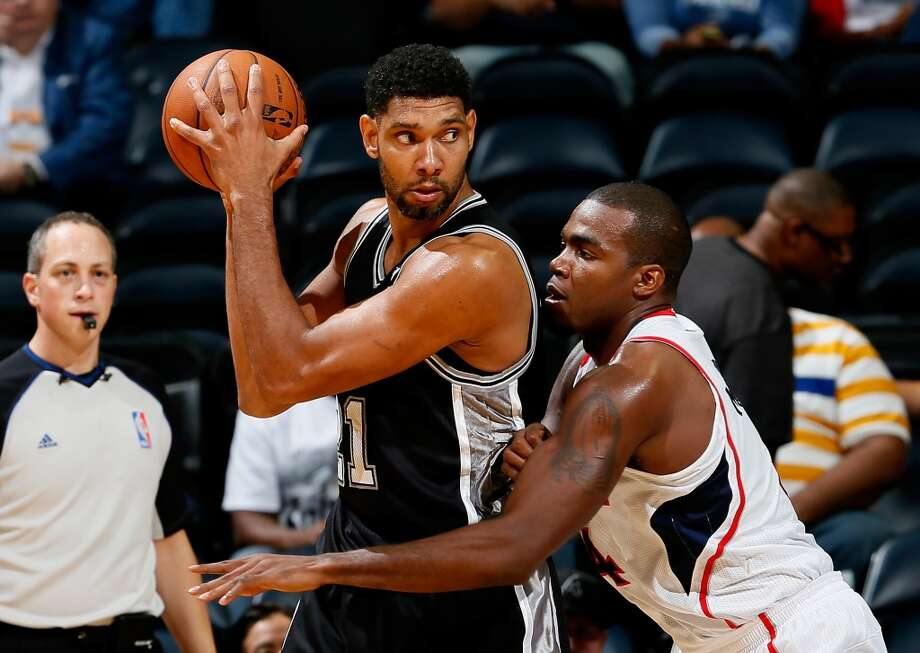 Paul Millsap #4 of the Atlanta Hawks defends against Tim Duncan #21 of the San Antonio Spurs at Philips Arena on October 17, 2013 in Atlanta, Georgia. Photo: Kevin C. Cox, Getty Images