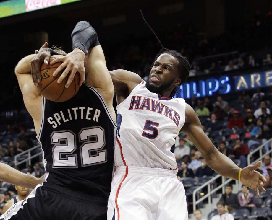 San Antonio Spurs power forward Tiago Splitter (22) and Atlanta Hawks small forward DeMarre Carroll (5) fight for a rebound in the first half of a preseason NBA basketball game, Thursday, Oct. 17, 2013 in Atlanta. Photo: John Bazemore, Associated Press