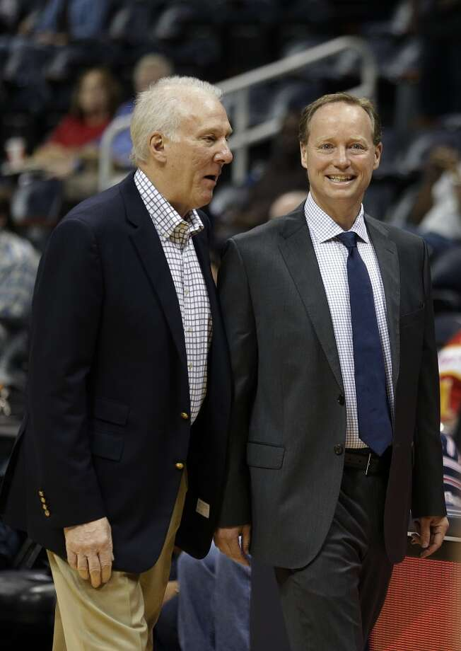 Atlanta Hawks head coach Mike Budenholzer, right, talks with San Antonio Spurs head coach Gregg Popovich before a preseason NBA basketball game, Thursday, Oct. 17, 2013 in Atlanta. Budenholzer was an assistant coach in San Antonio for 19 years before getting the Hawks' head coaching job. Photo: John Bazemore, Associated Press