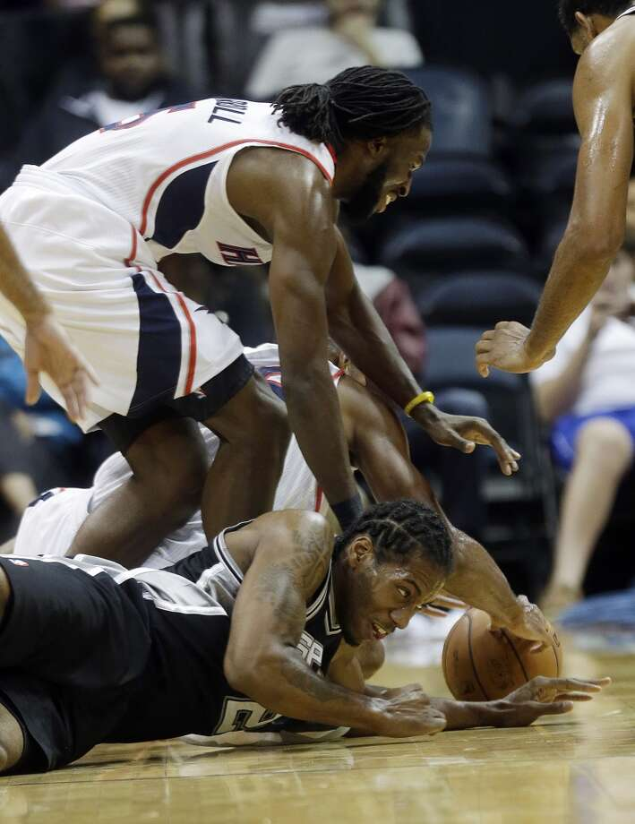 San Antonio Spurs small forward Kawhi Leonard (2) on floor, and Atlanta Hawks small forward DeMarre Carroll (5) battle for a loose ball half of a preseason NBA basketball game, Thursday, Oct. 17, 2013 in Atlanta. Photo: John Bazemore, Associated Press