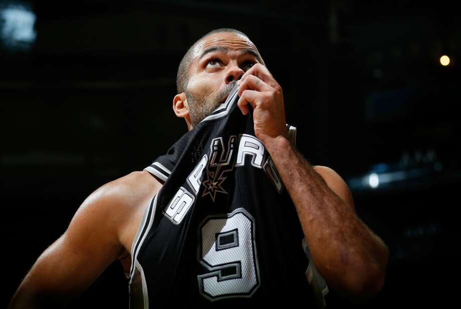 Tony Parker #9 of the San Antonio Spurs wipes sweat from his face during a timeout against the Atlanta Hawks at Philips Arena on October 17, 2013 in Atlanta, Georgia. Photo: Kevin C. Cox, Getty Images