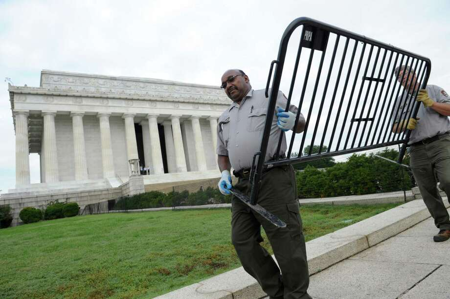 National Park Service employees remove barricades from the grounds of the Lincoln Memorial in Washington, Thursday, Oct. 17, 2013. Barriers went down at National Park Service sites and thousands of furloughed federal workers began returning to work throughout the country Thursday after 16 days off the job because of the partial government shutdown.(AP Photo/Susan Walsh) ORG XMIT: DCSW101 Photo: Susan Walsh / AP