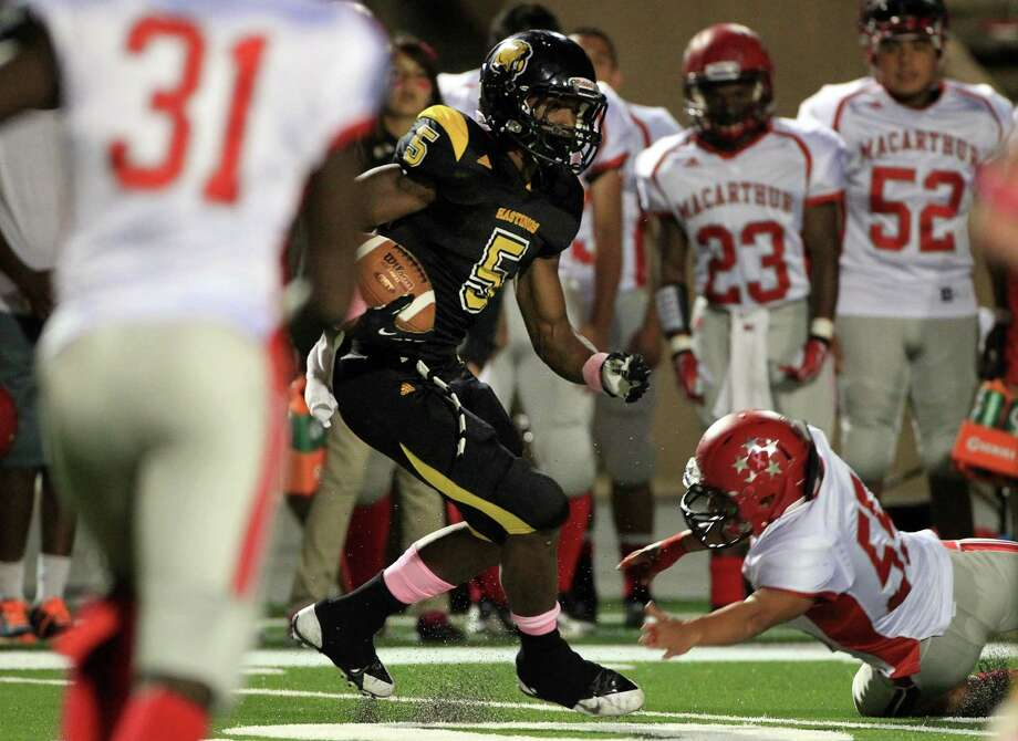 Alief Hastings Fighting Bears (#5) Joshua Wiggins gains yards as Aldine MacArthur Generals (#55) Joseph Cardenas attempts to tackle during the 1st quarter of the football at LeRoy Crump Stadium on Thursday, Oct. 17, 2013, in Houston. Photo: Mayra Beltran, Houston Chronicle / © 2013 Houston Chronicle