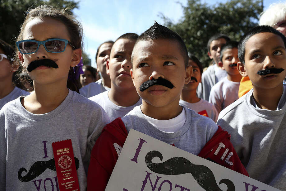 "Sporting fake facial hair and T-shirts emblazoned with the legend ""I mustache you not to do drugs,"" Loma Park Elementary students Daphne Bendele, 10 (from left), Rene Jimenez, 11, and Jonathan Martinez, 11, attend the rally. Photo: Photos By Lisa Krantz / San Antonio Express-News"