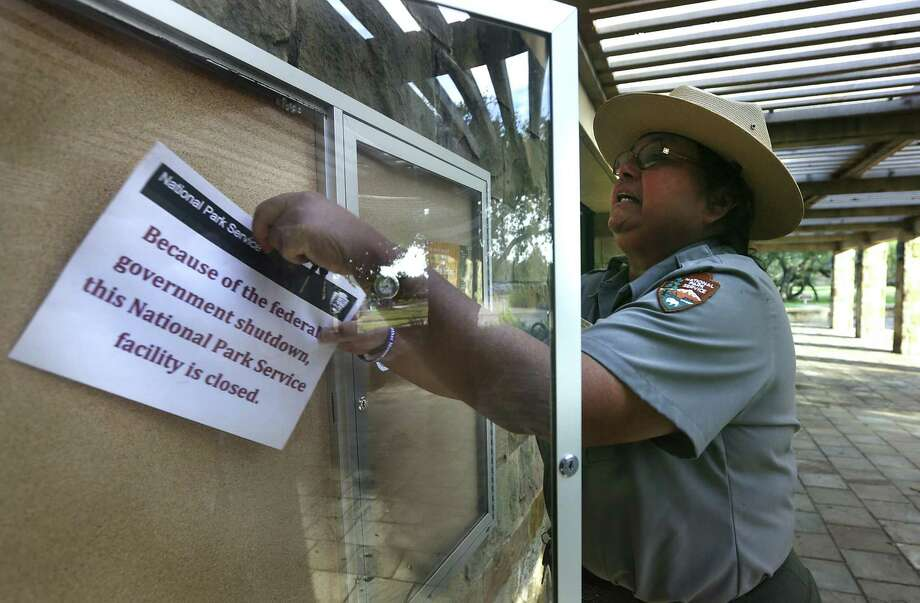 Anna Martinez-Amos, who's also a guide, takes down the shutdown notice in front of the Park Service office at Mission San José. The national park had been closed since Oct. 1.