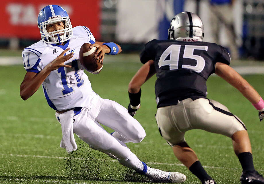 Mustang quarterback Moses Reynolds takes a hard cut away from Zach Wood as Jay plays Clark at Farris Stadium on October 17, 2013. Photo: Tom Reel, San Antonio Express-News