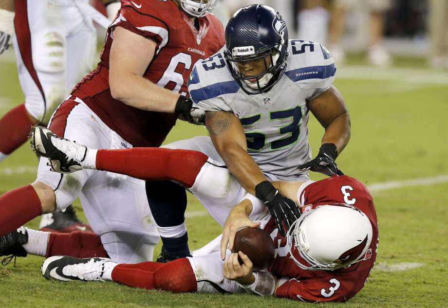 Seattle Seahawks' Malcolm Smith (53) gets up after sacking Arizona Cardinals' Carson Palmer (3) in the second half of an NFL football game on Thursday Oct. 17, 2013, in Glendale, Ariz.  The Seahawks defeated the Cardinals 34-22. (AP Photo/Ross D. Franklin) Photo: AP
