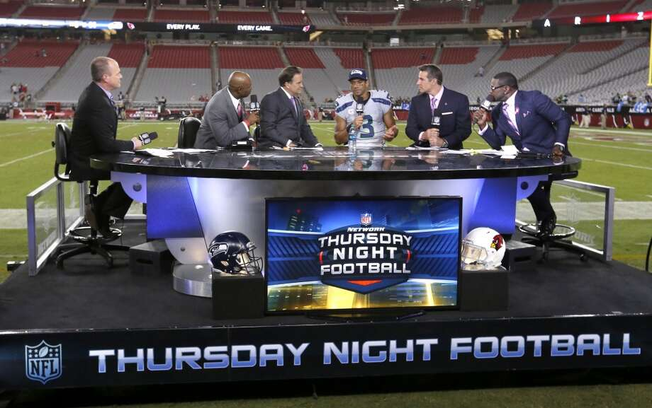 The NFL Network Thursday Night Football live crew from left, Rich Eisen, Dion Sanders, Steve Mariucci, Seattle Seahawks quarterback Russell Wilson, Kurt Warner and Michael Irvin talk after a NFL football game against the Arizona Cardinals and the Seattle Seahawks, Thursday, Oct. 17, 2013, in Glendale, Ariz. (AP Photo/Ross D. Franklin) Photo: AP
