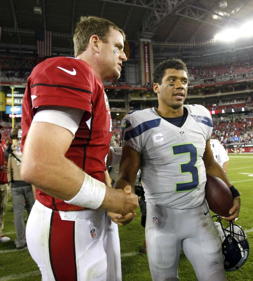 Arizona Cardinals quarterback Carson Palmer, left, and Seattle Seahawks quarterback Russell Wilson greet each other during after an NFL football game, Thursday, Oct. 17, 2013, in Glendale, Ariz. The Seahawks won 34-22. (AP Photo/Rick Scuteri) Photo: AP