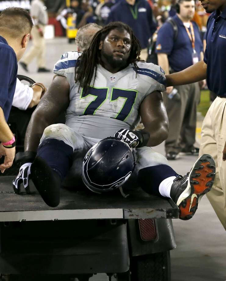 Seattle Seahawks guard James Carpenter leaves the field after being injured against the Arizona Cardinals during the second half of an NFL football game, Thursday, Oct. 17, 2013, in Glendale, Ariz. (AP Photo/Ross D. Franklin) Photo: AP