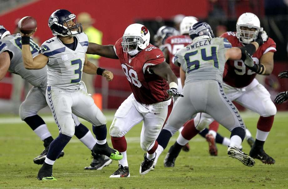 Seattle Seahawks quarterback Russell Wilson (3) throws under pressure from Arizona Cardinals defensive end Frostee Rucker (98) during the second half of an NFL football game, Thursday, Oct. 17, 2013, in Glendale, Ariz. (AP Photo/Rick Scuteri) Photo: AP