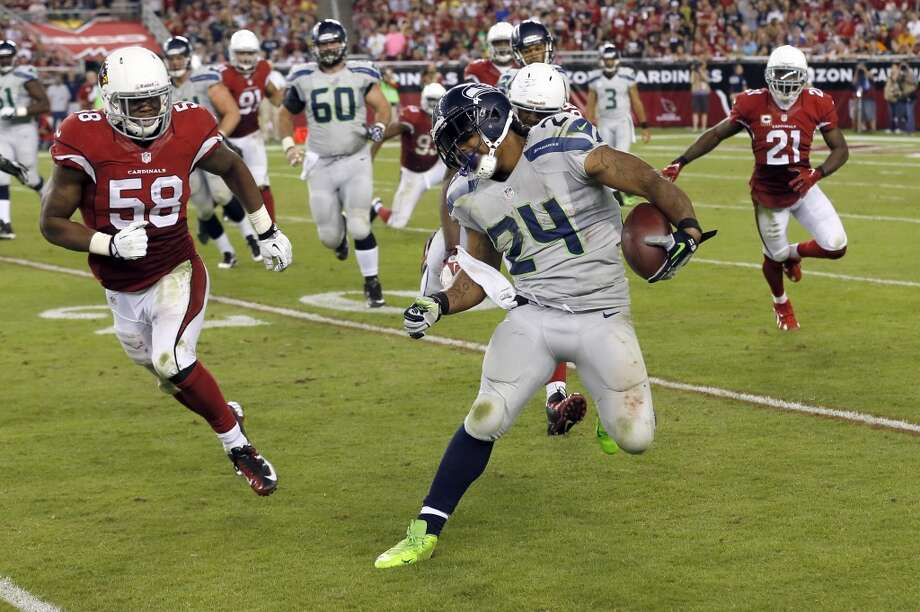 Seattle Seahawks running back Marshawn Lynch (24) tries to avoid Arizona Cardinals inside linebacker Daryl Washington (58) during the second half of an NFL football game, Thursday, Oct. 17, 2013, in Glendale, Ariz. (AP Photo/Ross D. Franklin) Photo: ASSOCIATED PRESS