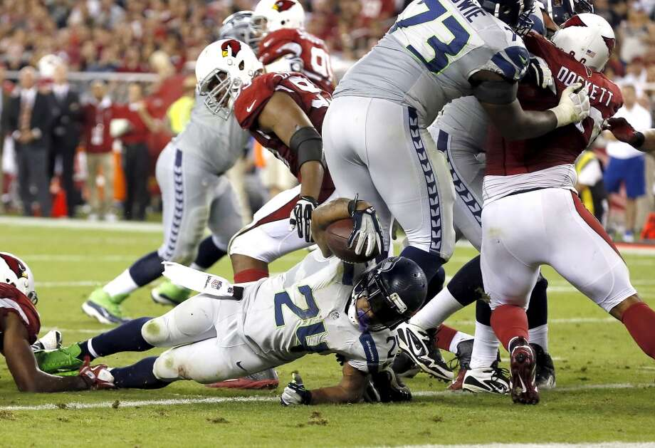 Seattle Seahawks running back Marshawn Lynch (24) falls into the end zone for a touchdown as Arizona Cardinals inside linebacker Karlos Dansby (56) defends during the second half of an NFL football game, Thursday, Oct. 17, 2013, in Glendale, Ariz. (AP Photo/Ross D. Franklin) Photo: AP