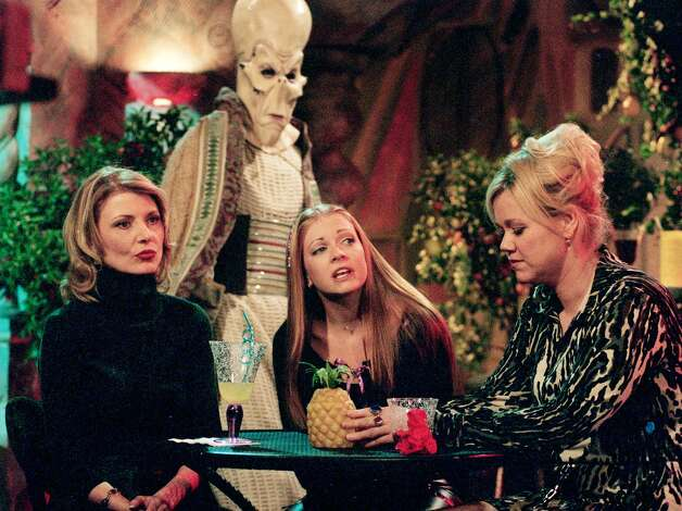 ADVANCE FOR WEEKEND EDITIONS OCT. 20-22--Melissa Joan Hart, star of the WB network series 'Sabrina, the Teenage Witch,' sits with series co-stars Beth Broderick, left, and Caroline Rhea, who play fellow witches Zelda and Hilda, respectively, as an alien figure passes behind them during a break from shooting on the series set at Paramount Studios Oct. 6, 2000, in Los Angeles. The sitcom will mark its 100th episode on Friday, Oct. 27. Photo: REED SAXON, AP / AP