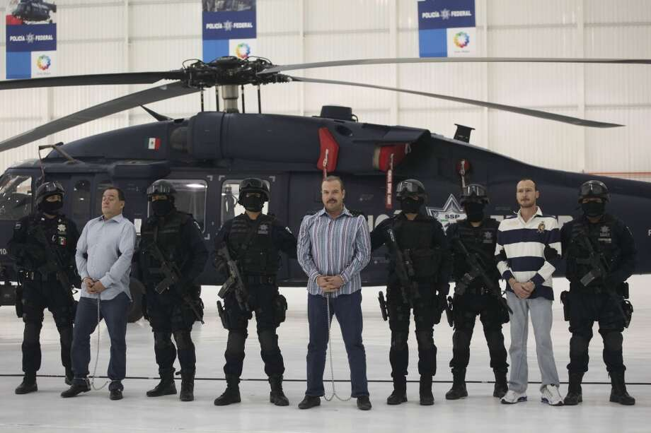 "Federal Police officers escort accused drug trafficker Carlos Montemayor, center, and two other alleged drug cartel members in Mexico City, Wednesday, Nov. 24, 2010. According to Federal Police Montemayor took over the criminal organization led by Edgar Valdez Villareal, aka ""La Barbie"", a reputed US-born kingpin after he was detained. Photo: Alexandre Meneghini, AP"