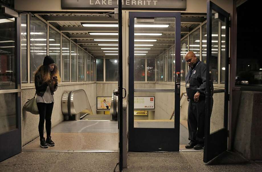 Richelle Anderson of Hayward watches as BART station agent Edmund Buenger performs his shut down duties at Lake Merritt station early Friday after midnight before the strike begins. People involved with negotiations between BART and its unions declared an impasse following nearly 30 hours of negotiations on Thursday, and the unions will strike at midnight. BART negotiations failed to yield an agreement on Thursday, October 17, 2013, in Oakland, Calif. Photo: Carlos Avila Gonzalez, The Chronicle
